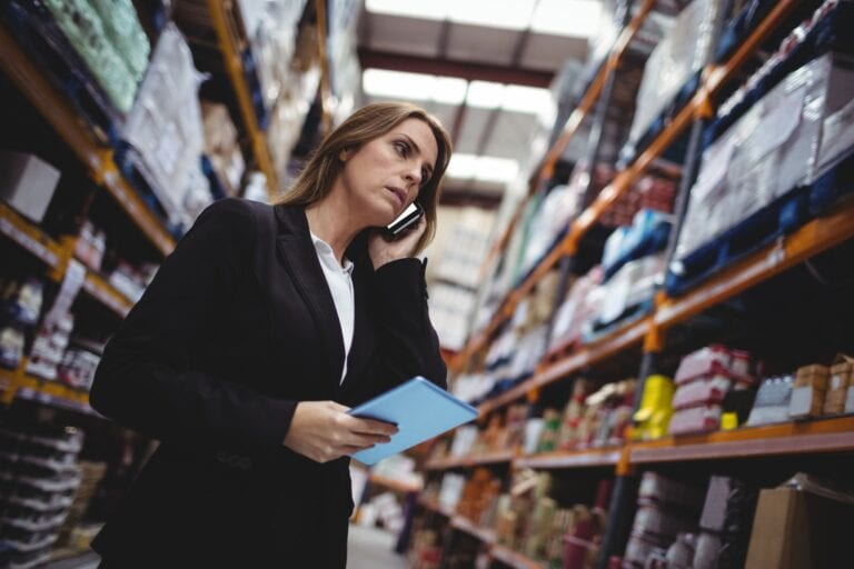 Businesswoman on a phone call in warehouse